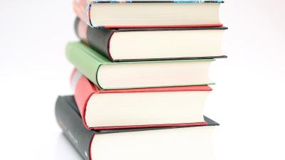 Några ganska tjocka böcker ligger i en hög.