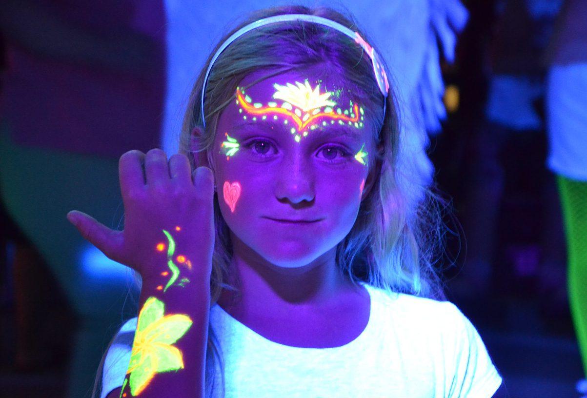 En flicka med självlysande färg i ansiktet och på armen