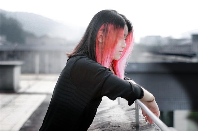 En flicka med svart och rosa hår. Hon står vid ett räcke.