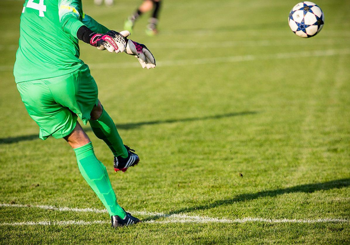 En målvakt i gröna kläder som sparkar iväg en fotboll.
