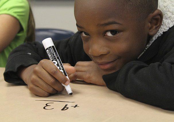 En pojke som löser en matteuppgift, han tittar in i kameran.