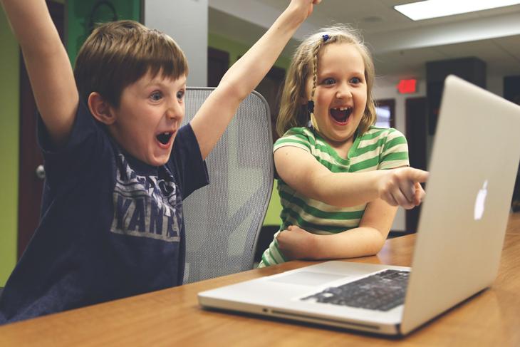 Två glada barn som tittar på en laptop