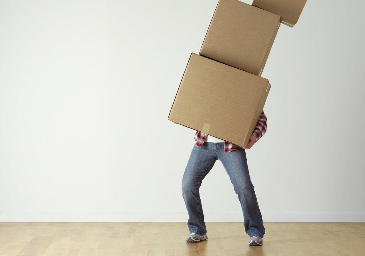 en person som håller i tre flyttlådor