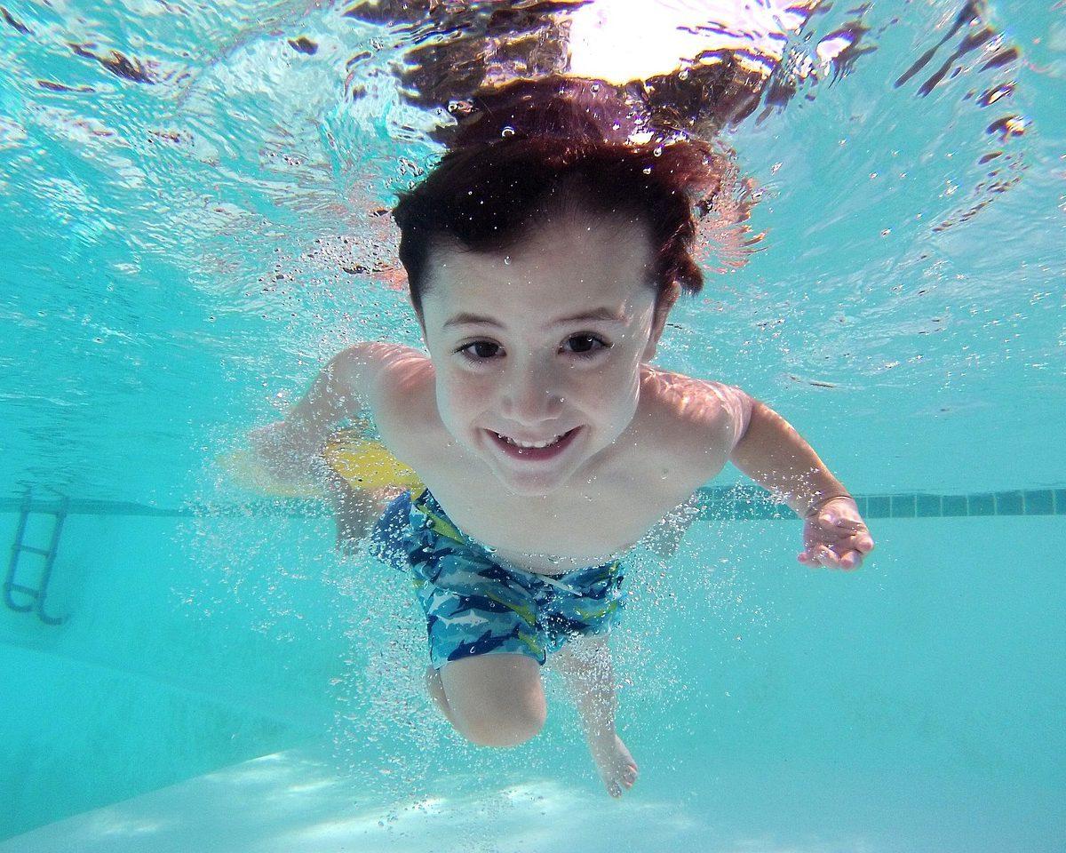 en pojke som simmar under vatten