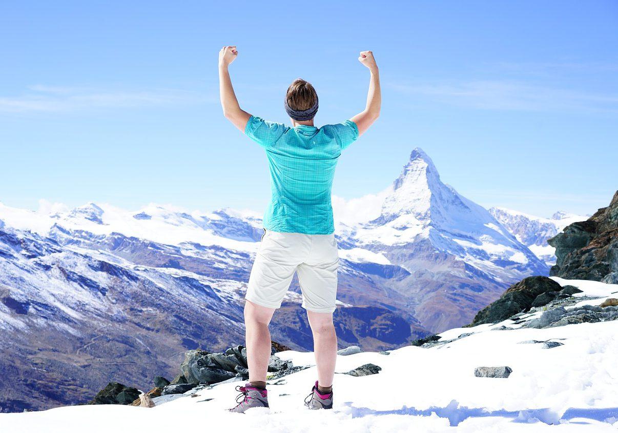 En person som syns bakifrån med armarna i luften. Personen står på ett snötäckt berg.