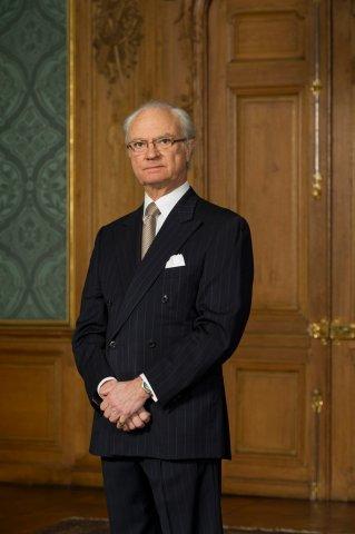 Kungen står framför en stor brun dörr. Han ser allvarlig ut och tittar in i kameran. Han har grått tunt hår, glasögon och kostym med slips.
