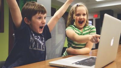 Två barn sitter framför en bärbar dator. Båda ser jätteglada ut. Den ena ler stort och pekar på skärmen. Den andra håller armarna över huvudet och ropar glatt.