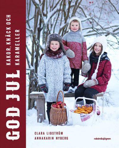 Tre barn poserar ute i snön. Framför sig har de en korg med lussebullar och en korg med äpplen.