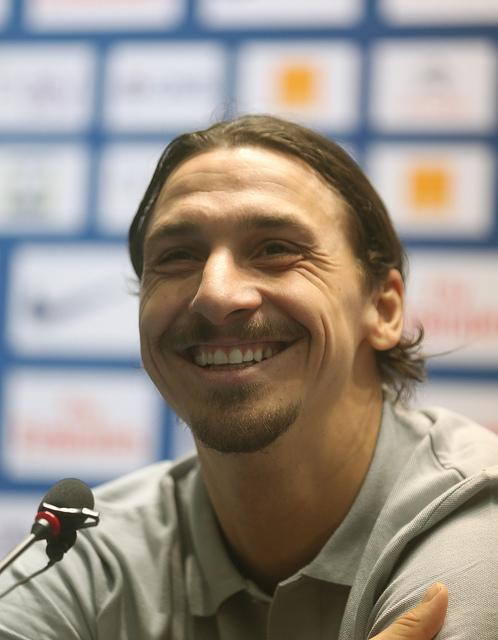 Zlatan ler stort. Han har håret i en hästsvans och har en grå tröja på sig.