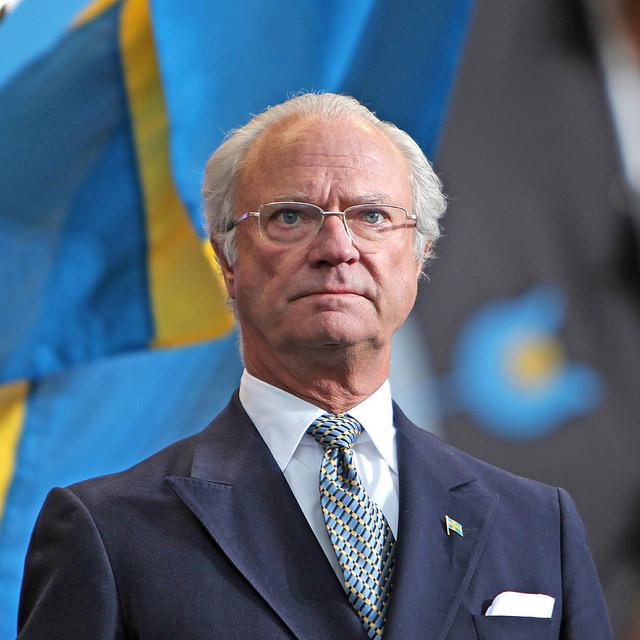 Kungen står framför några svenska flaggor. Han ser allvarlig ut och tittar ut i fjärran. Han har glest vitt hår, glasögon och en kostym med slips.