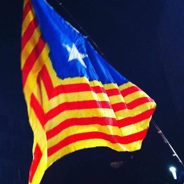 En röd- och gulrandig flagga. På ena sidan är det en blå triangel med en vit stjärna på.