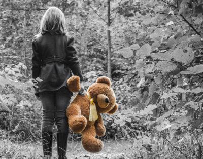 En flicka som står med ryggen mot kameran. Hon håller i en stor nallebjörn.