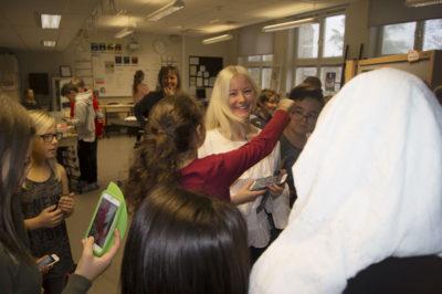 En flicka med hästsvans och röd tröja sträcker ut armen för att krama om Natalie. Andra elever står runt om, de håller i sina mobiltelefoner.
