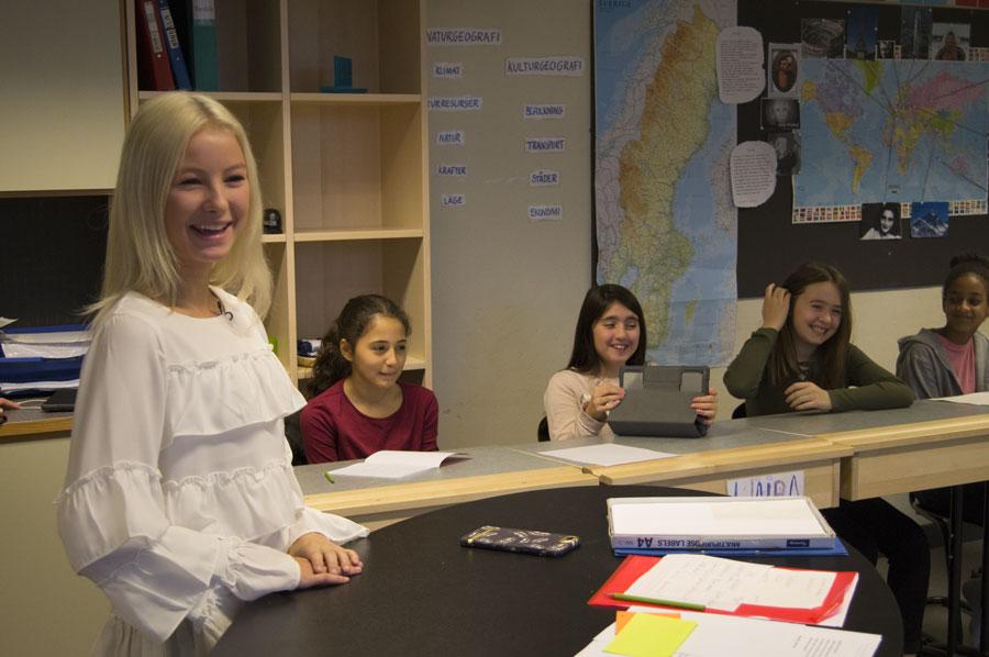 Natalie Danielsson står vid ett bord i klassrummet, hon har en vit tröja med volanger på sig. Eleverna sitter vid sina bänkar.