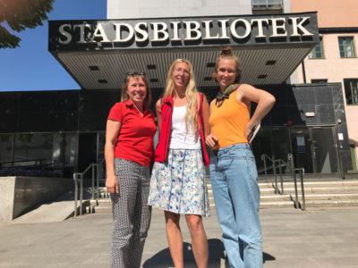 MiniBladets grundare Maria McShane står tillsammans med bibliotekarie Hedvig Andersson och reporter Nanna Salemark framför Eskilstuna stadsbibliotek.