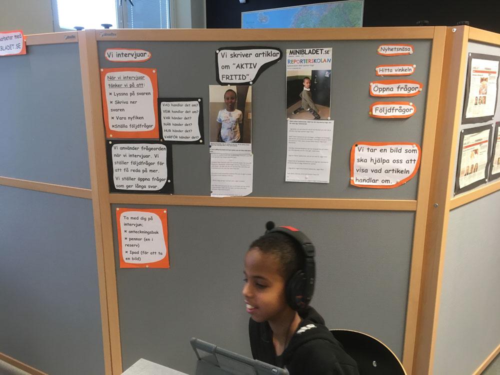 En kille sitter framför en dataskärm med hörlurar på sig. Bakom honom syns en vägg där det hänger massa lappar.