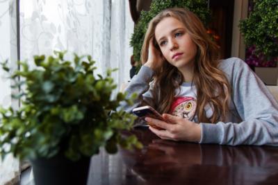 En flicka som tittar ut genom ett fönster. Hon har brunt långt hår och en grå tröja på sig. I den vänstra handen håller hon i en smartphone.