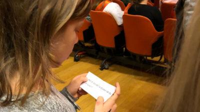 En flicka med grå tröja och mörkblont hår läser en lapp