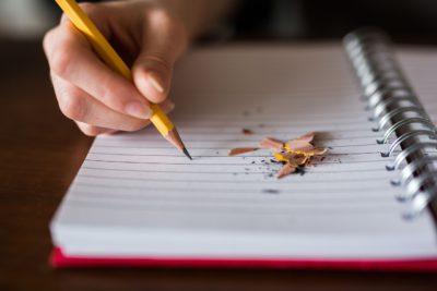 Ett block med randigt papper och en hand som håller i en gul penna