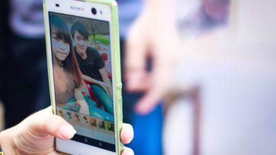 En hand som håller i en smartphone. På skärmen syns ett foto på en flicka och en pojke.