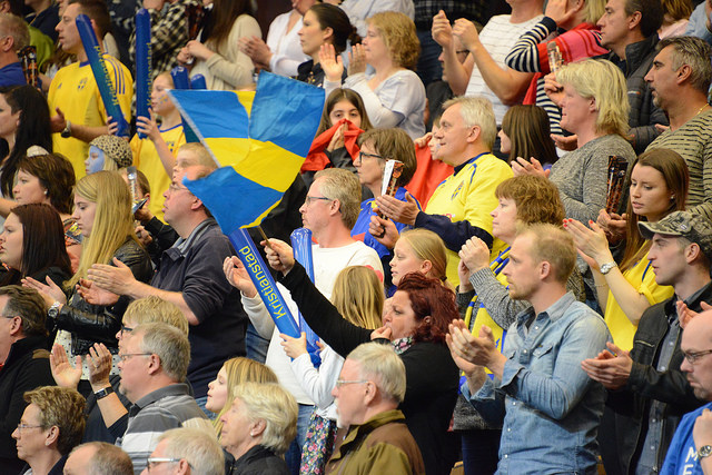 Massa människor står i publiken. En av dem viftar med en stor svensk flagga.