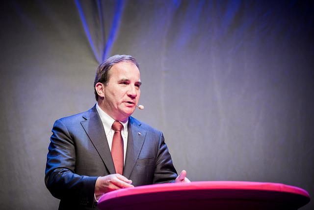 Stefan Löfven står i en talarstol. Han har kort hår, slips och en mikrofon vid munnen.