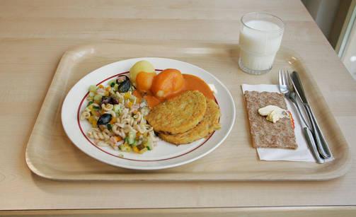 En bricka där det står en tallrik med mat, ett glas mjölk och en knäckebrödsmacka.