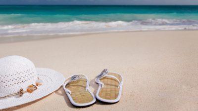 Hatt och sandaler på en strand