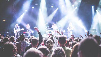 Publikhav tittar mot scenen där artister spelar musik