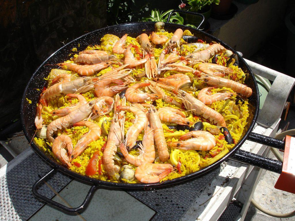 Den spanska maträtten paella. Gult ris med musslor och dekorerad med räkor.