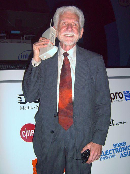 Bild: En äldre man håller en gammal mobiltelefon. Mobilen är lika stor som hans huvud och har en antenn.