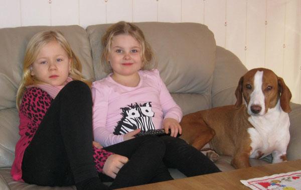 Två flickor och en hund som sitter i en soffa.