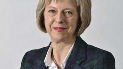 Theresa May i rutig kavaj ler.