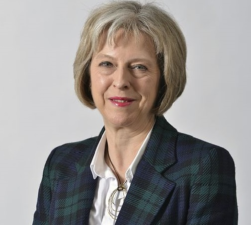 Theresa May i rutig kavaj ler.