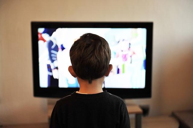 En pojke sitter framför en tv