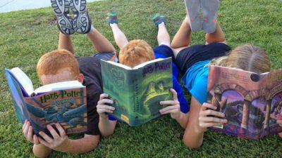Tre barn ligger på en gräsmatta. Vi ser inte deras ansikten eftersom de håller upp böcker för ansiktena och läser.