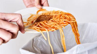 Ett par händer som skrapar ner spaghetti från en tallrik ner i en soptunna.