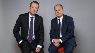 Två män i kostymer och slips som sitter på varsin pall.