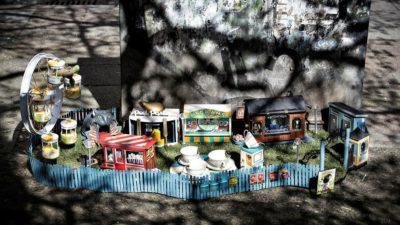 """Ett tivoli i miniatyrformat. Tivolit har flera små bodar och ett pariserhjul. Det är omgärdat av ett blått staket och över ingången är en skylt där det står """"Tjoffsans tivoli""""."""