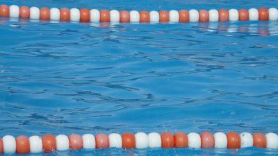 Blått vatten i en bassäng och linor som gränsar av olika simbanor.