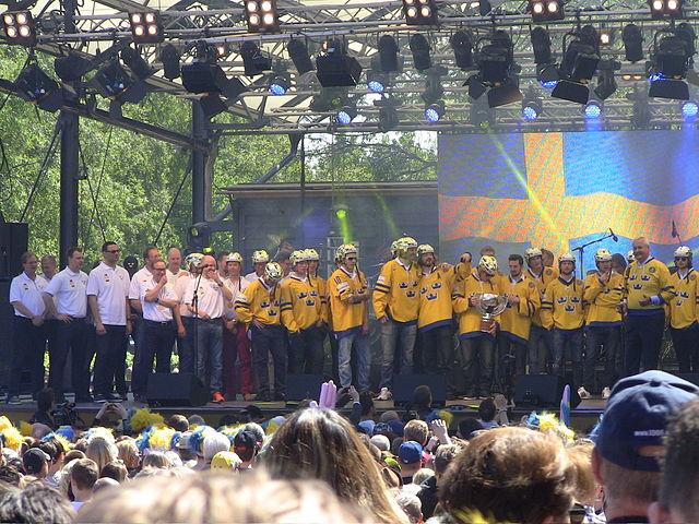 Svenska landslaget i hockey står på en scen framför en stor publik.
