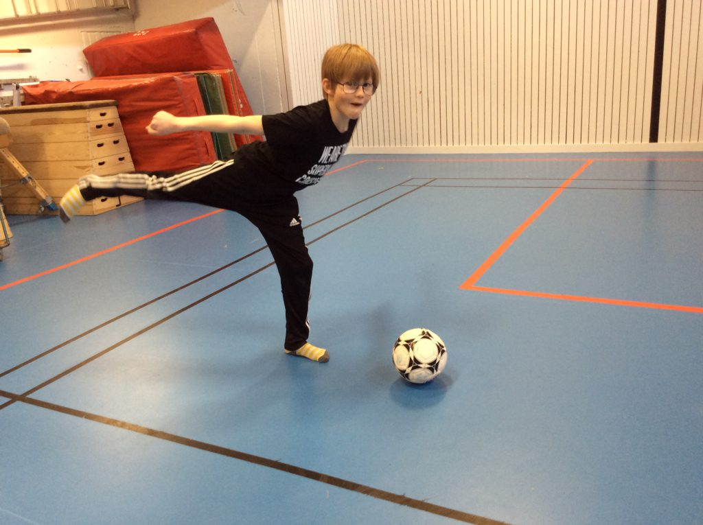 Noel står i en idrottshall med ett höjt ben och ska precis sparka på en fotboll.