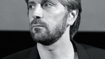 Ruben Östlund sns från axlarna ch uppåt. Han har halvlångt hår, skägg ch svart kavaj.