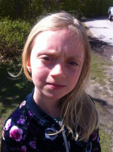 Elsa står utomhus i solen. Hon har långt blont hår och rynkar pannan.