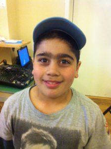 Atila står i ett klassrum. Han har en keps och en grå t-shirt.