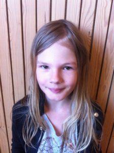 Matilda står framför en vägg. Hon har långt blont hår och en svart jacka.