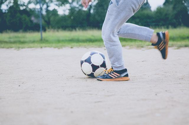 Tva fotter som springer med en fotboll framf;r sig.