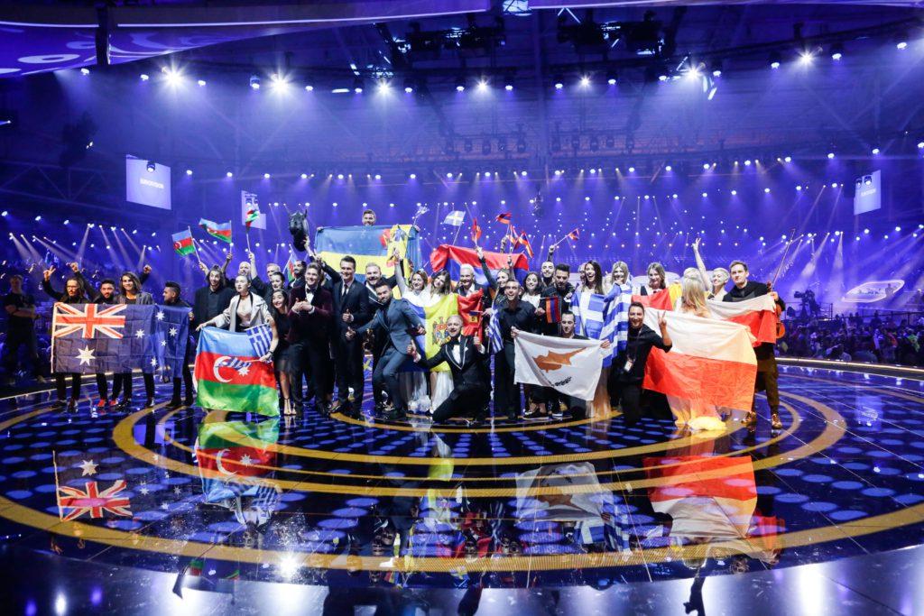 De tio vinnarna står i en klunga med sitt lands flagga i händerna. I bakgrunden är det massa strålkastare.