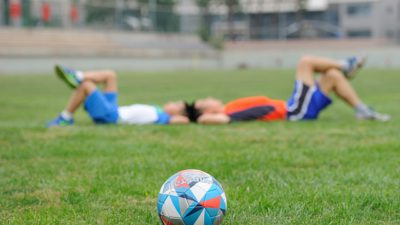 En fotboll ligger på en gräsmatta. I bakgrunden ligger två barn med huvudena mot varandra och benen korsade.