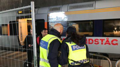 Två poliser i reflexväst står framför ett tåg och kollar en mans id.